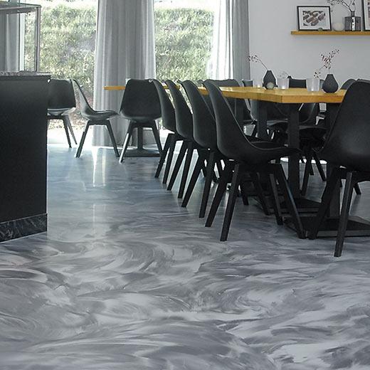 Sitzgelegenheiten in einem Café mit Wischtechnik-Bodenbelag aus Kunstharz