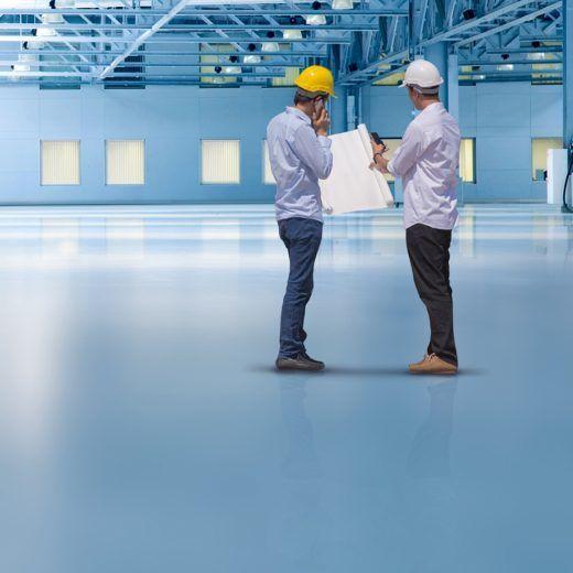 Beschichtete Halle mit zwei Bauherren mit einem Plan in der Hand