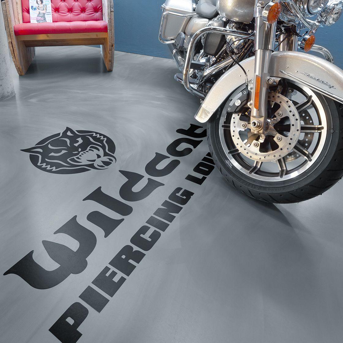 Eingearbeitetes Logo im Fußboden eines Tattoostudios mit einem Motorrad und weiteren dekorativen Elementen einer taubenblauen Wand mit Ziegelsteinen