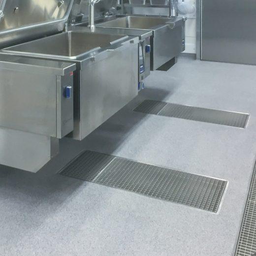 Industrielle Großküche mit Edelstahl-Oberflächen und abgestreutem Bodenbelag