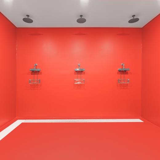 Rote Wand- und Bodenbeschichtung der Duschkabinen mit weißer Ablaufrinne