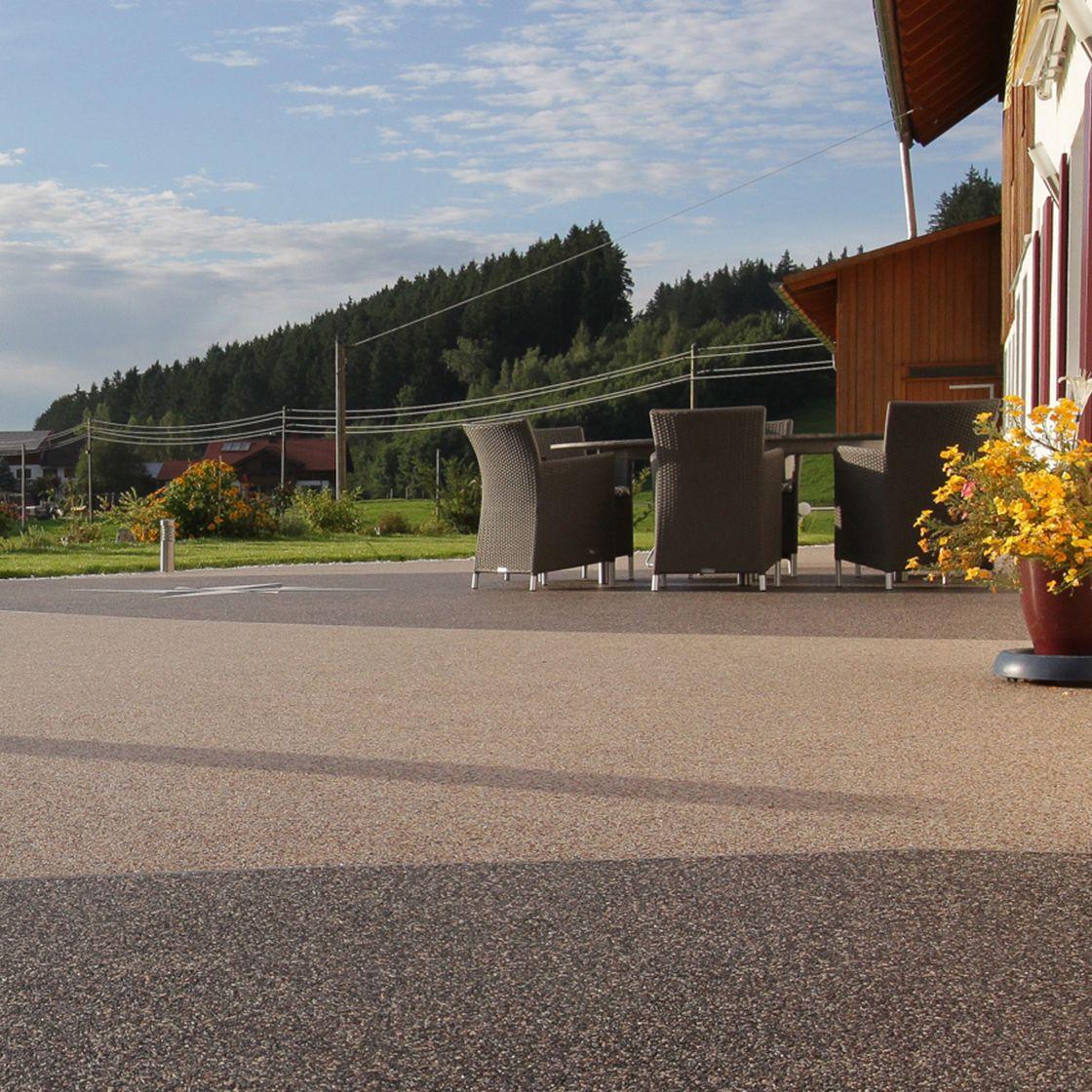 Außenbereich auf einer Terrasse mit Sitzmöbeln und einem Steinteppich als Boden